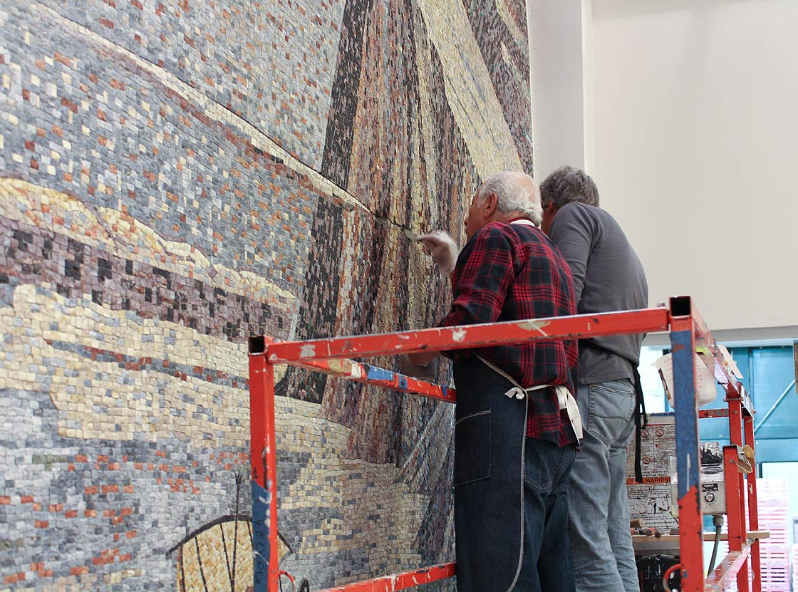 Schiavo (left)  and Miotto (right) installing the center panel in the atrium of the Newark Museum