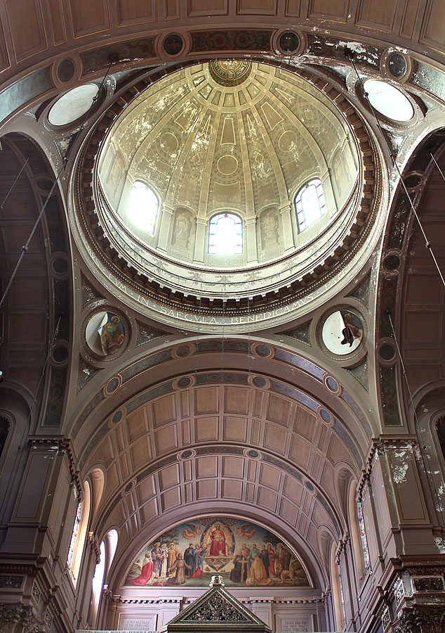 Main sanctuary in 2014 with tympanum visible above baldacchino. The canvas roundels depicting Mark (left) and Matthew (right) have peeled away from the plaster. The two other Evangelists are missing.